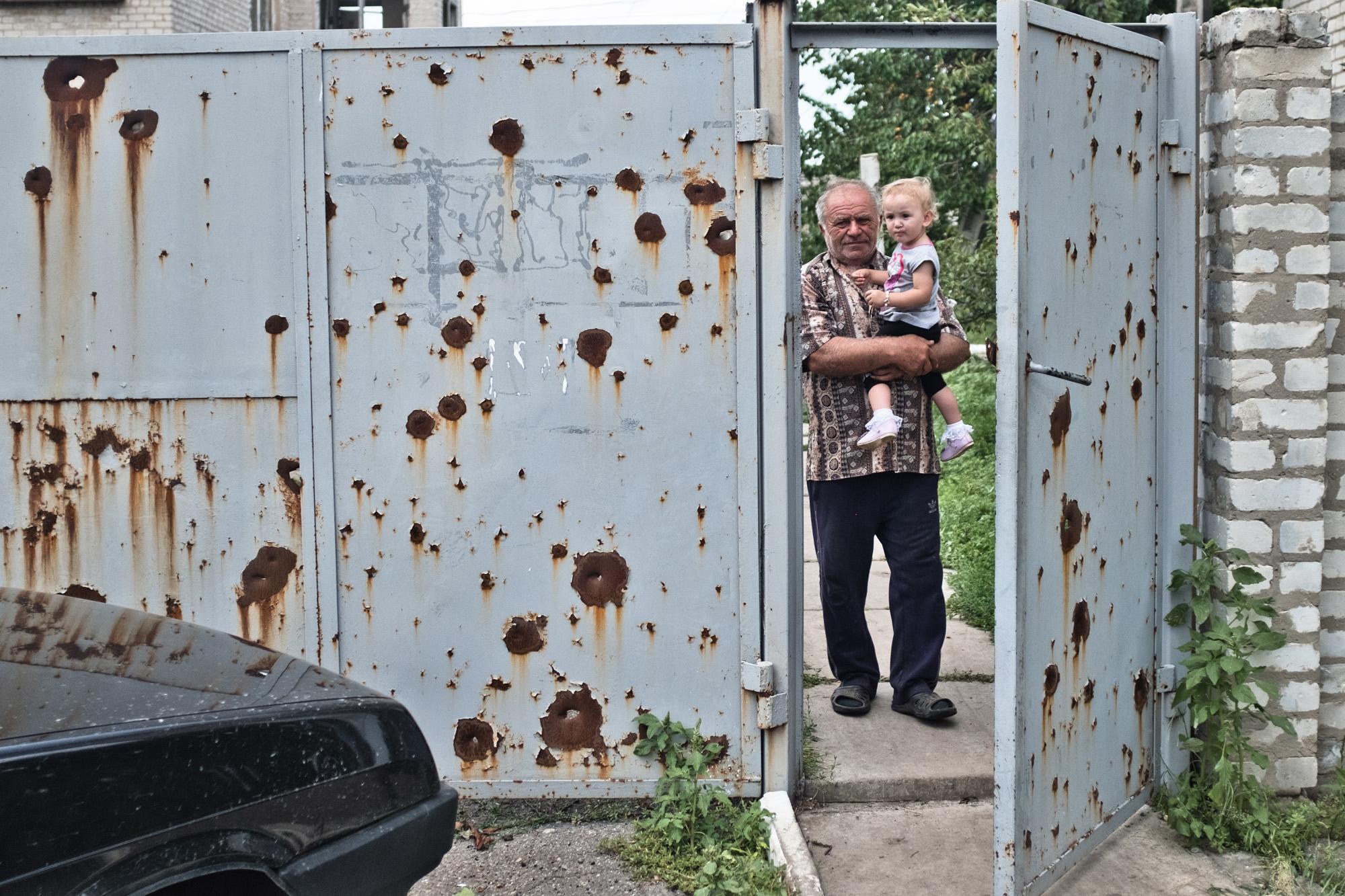 Ein Großvater hält seine Enkeltochter in Stanyzja Luhanska im Arm. Am Tor zu sehen: zahlreiche Einschusslöcher.